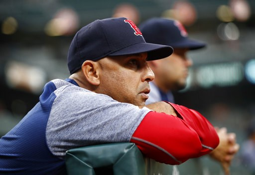 (AP Photo/Patrick Semansky, File). FILE - In this July 24, 2018, file photo, Boston Red Sox manager Alex Cora leans against the dugout rail during the second inning of the team's baseball game against the Baltimore Orioles in Baltimore. The Red Sox rew...