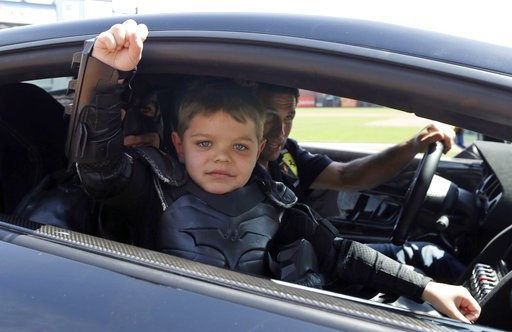 (AP Photo/Eric Risberg, Pool). In this file photo from Tuesday, April 8, 2014, Miles Scott, dressed as Batkid, gestures as he sits in the Batmobile after throwing the ceremonial first pitch before a baseball game between the San Francisco Giants and th...