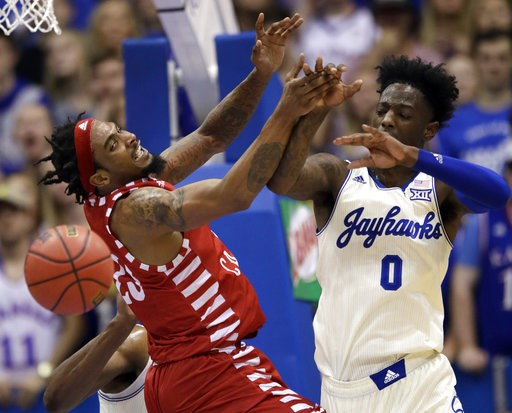 (AP Photo/Orlin Wagner). Louisiana Lafayette forward JaKeenan Gant, left, tries to rebound against Kansas guard Marcus Garrett (0) during the first half of an NCAA college basketball game in Lawrence, Kan., Friday, Nov. 16, 2018.