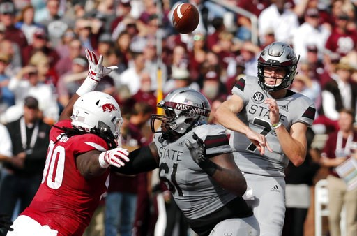 (AP Photo/Rogelio V. Solis). Mississippi State quarterback Nick Fitzgerald (7) passes against an on rushing Arkansas defender during the first half of an NCAA college football game in Starkville, Miss., Saturday, Nov. 17, 2018.