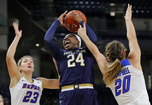 (AP Photo/Jim Young). Notre Dame's Arike Ogunbowale, center, goes to the basket between DePaul's Dee Bekelja, left, and Kelly Campbell during the first half of an NCAA college basketball game, Saturday, Nov. 17, 2018, in Chicago.