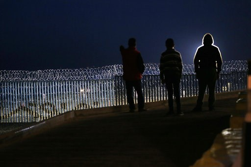 (AP Photo/Marco Ugarte). Residents stand on a hill before barriers, wrapped in concertina wire, separating Mexico and the United States, where the border meets the Pacific Ocean, in Tijuana, Mexico, Saturday, Nov. 17, 2018. Many of the nearly 3,000 mig...