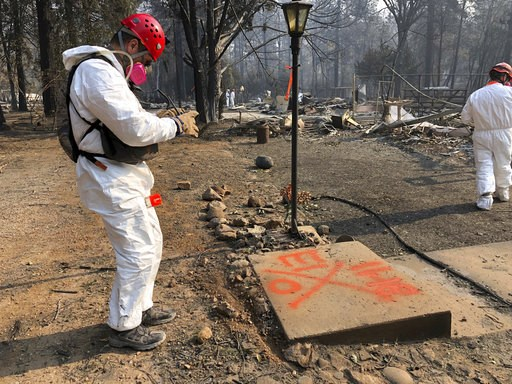 (AP Photo/Sudhin Thanawala). A volunteer member of an El Dorado County search and rescue team photographs the orange spray paint that marks the ruins of a home to show that no human remains were found at the location in Paradise, Calif., Sunday, Nov. 1...
