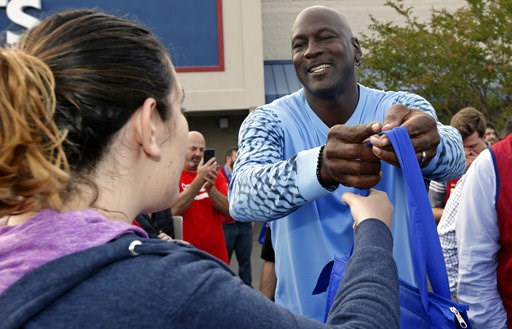 (AP Photo/Gerry Broome). Charlotte Hornets owner Michael Jordan greets people and hands out food for Thanksgiving to members of the community in Wilmington, N.C., Tuesday, Nov. 20, 2018.