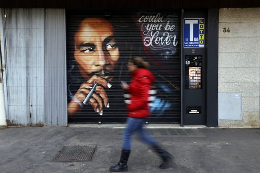 (AP Photo/Gregorio Borgia). A woman walks past a mural depicting reggae music icon Bob Marley painted on the rolling shutter of a Tobacconist shop in Rome, Thursday, Nov. 28, 2018.