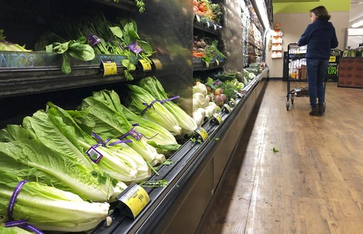 (AP Photo/Mark J. Terrill, File). FILE - In this Nov. 20, 2018 file photo, romaine lettuce sits on the shelves as a shopper walks through the produce area of an Albertsons market in Simi Valley, Calif.  After repeated food poisoning outbreaks linked to...