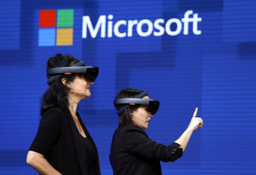 (AP Photo/Elaine Thompson, File). FILE- In this May 11, 2017, file photo, members of a design team at Cirque du Soleil demonstrate use of Microsoft's HoloLens device in helping to virtually design a set at the Microsoft Build 2017 developers conference...