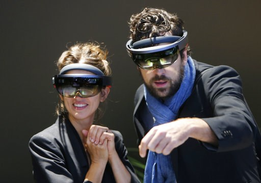 (AP Photo/Michael Probst, File). FILE- In this Sept. 24, 2017, file photo people use Microsoft Hololens to get an impression of Mercedes accessories on the stand of Mercedes-Benz during the first media day of the International Frankfurt Motor Show IAA ...