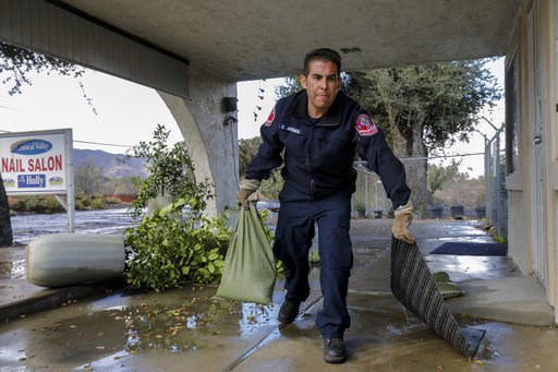 (Irfan Khan/Los Angeles Times via AP). Corona fireman Charlie Apodaca places sand bags at a business to protect it from flooding along Temescal Canyon Road Thursday, Nov. 29, 2018, in Corona, Calif. Forecasters say the weather system that has been rain...