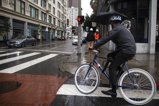 (Kent Nishimura/Los Angeles Times via AP). With cloudy skies and rain falling, a bike rider turns off Broadway, as people walk in downtown Los Angeles on Thursday, Nov. 29, 2018. The storm has knocked out power and flooded roadways across Southern Cali...