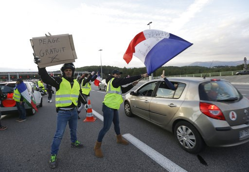 "(AP Photo/Claude Paris, File). FILE - In this Nov. 19, 2018 file photo, protesters known as the yellow jackets, wave a French flag and a poster reading ""Free toll"" as they open the toll gates on a motorway in Antibes, southern France. France's prime mi..."