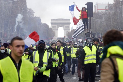 (AP Photo/Kamil Zihnioglu, File). FILE - In this Nov 19, 2018 file picture, demonstrators, known as the yellow jackets, invade the famed Champs-Elysees avenue in Paris, France, as they protest against the rise in fuel prices. France's prime minister Ed...