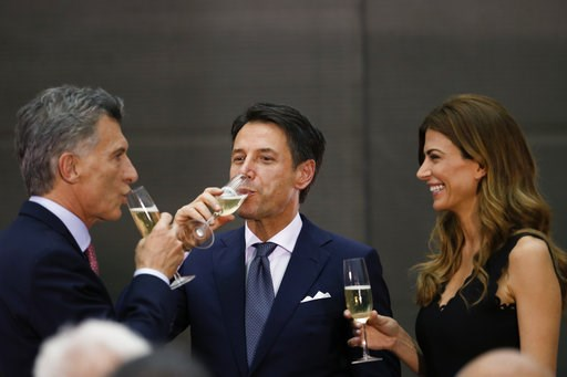 (AP Photo/Natacha Pisarenko). Argentina's President Mauricio Macri, left, and Argentina's first lady Juliana Awada, right, share a glass of champagne with Italy's Prime Minister Giuseppe Conte at the presidential palace in Buenos Aires, Argentina, Thur...