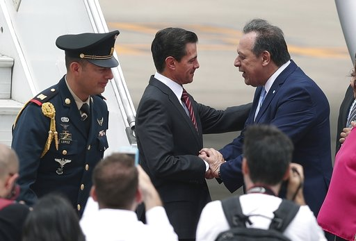 (AP Photo/Martin Mejia). Mexico's President Enrique Pena Nieto, center, is received by Argentina's Tourism Secretary, Gustavo Santos, at the Ministro Pistarini international airport in Buenos Aires, Argentina, Thursday, Nov. 29, 2018. Leaders from the ...