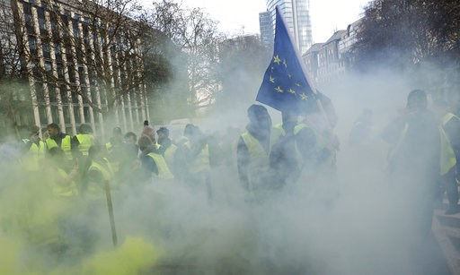 (AP Photo/Francisco Seco). Demonstrators, called the yellow jackets, holds up an EU flag during a protest against rising fuel prices in Brussels, Friday, Nov. 30, 2018
