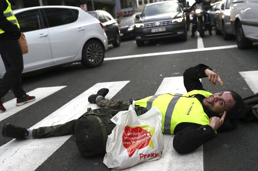 (AP Photo/Francisco Seco). A demonstrator, called the yellow jackets, lays in a pedestrian crosswalk as he protests against rising fuel prices in Brussels, Friday, Nov. 30, 2018