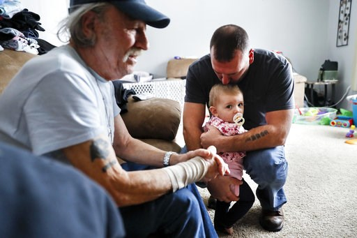 (AP Photo/John Minchillo). In this Nov. 28, 2018 photo, Tom Wolikow, right, holds his daughter Annabella alongside his father John, left, at their home in Warren, Ohio. It was working-class voters who bucked the area's history as a Democratic stronghol...
