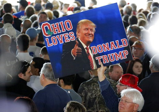 (AP Photo/Gene J. Puskar). In this March 14, 2016 photo, a supporter of Republican presidential candidate Donald Trump holds a sign during a plane-side rally at Youngstown-Warren Regional Airport in Vienna, Ohio. It was working-class voters who bucked ...