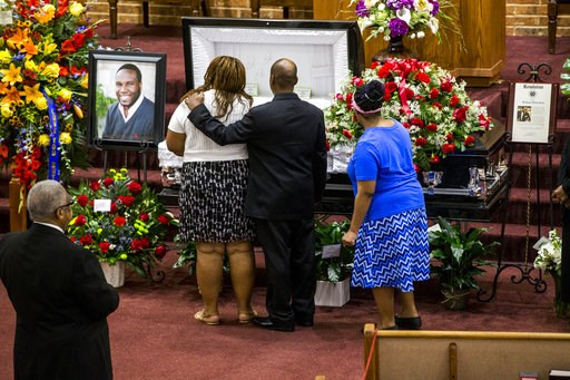 (Shaban Athuman/The Dallas Morning News via AP, File). FILE - In this Sept. 13, 2018, file photo, mourners console one another during the public viewing before the funeral of Botham Shem Jean at the Greenville Avenue Church of Christ in Richardson, Tex...