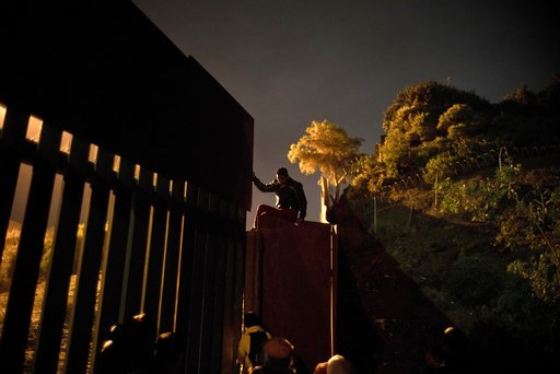 (AP Photo/Ramon Espinosa). A Honduran migrant climbs the border wall separating Tijuana, Mexico and San Diego, before crossing to the U.S with his son in Tijuana, Mexico, Thursday, Nov. 29, 2018. Aid workers and humanitarian organizations expressed con...
