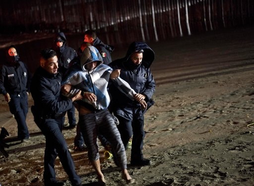(AP Photo/Ramon Espinosa). Mexican police help a Honduran migrant who tried to cross the U.S. border by the sea in Tijuana beach, Mexico, Thursday, Nov. 29, 2018. Aid workers and humanitarian organizations expressed concerns Thursday about the unsanita...