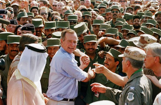 (AP Photo/J. Scott Applewhite, File). FILE - In this Nov. 22, 1990 file photo, President George H.W. Bush is greeted by Saudi troops and others as he arrives in Dhahran, Saudi Arabia, for a Thanksgiving visit. Bush died at the age of 94 on Friday, Nov....