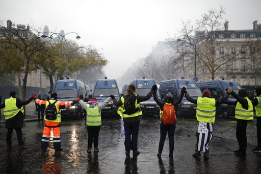 (AP Photo/Kamil Zihnioglu). Demonstrators wearing yellow jackets make a chain in front of police forces near the Champs-Elysees avenue during a demonstration Saturday, Dec.1, 2018 in Paris. French authorities have deployed thousands of police on Paris'...