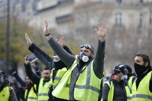 (AP Photo/Kamil Zihnioglu). Masked demonstrators wearing yellow jackets raise their hands near the Champs-Elysees avenue during a demonstration Saturday, Dec.1, 2018 in Paris. Scuffles broke out between some French protesters angry over rising taxes an...