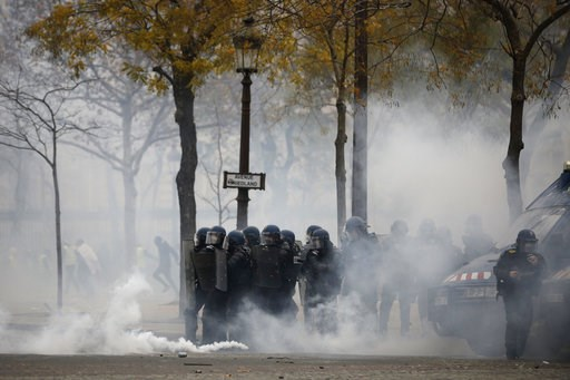 (AP Photo/Kamil Zihnioglu). French riot police officers take position amid tear gas during a demonstration Saturday, Dec. 1, 2018 in Paris. French authorities have deployed thousands of police on Paris' Champs-Elysees avenue to try to contain protests ...