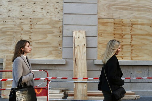 (AP Photo/Thibault Camus). Women walk past barricaded shop windows on the Champs Elysees avenue, in Paris, Friday, Nov. 30, 2018. Workers were barricading shop windows along Paris' famed Champs-Elysees Avenue on Friday, a day before a protest against g...