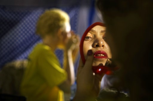(AP Photo/Ben Curtis). A contestant checks her makeup in a mirror as she prepares to perform in the Mr. & Miss Albinism East Africa contest, organized by the Albinism Society of Kenya, in Nairobi, Kenya Friday, Nov. 30, 2018. The event aims to prom...