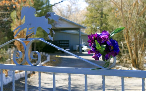 (AP Photo/Susan Montoya Bryan, File). FILE - In this Jan. 21, 2013, file photo, a bouquet of flowers adorns the entrance to a home on where a couple and their three young children were found shot to death south of Albuquerque, N.M. Nehemiah Griego who ...