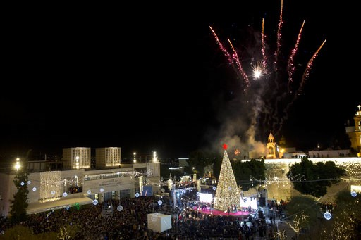 (AP Photo/Majdi Mohammed). Palestinian Christians celebrate the lighting of a Christmas tree in Manger Square, outside the Church of the Nativity in the West Bank town of Bethlehem,, Saturday, Dec. 1, 2018.