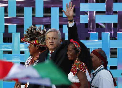 (AP Photo/Moises Castillo). CORRECTS BYLINE - Mexico's new President Andres Manuel Lopez Obrador walks with indigenous religious leaders for a traditional indigenous ceremony at the Zocalo, in Mexico City, Saturday, Dec. 1, 2018. Mexicans are getting m...