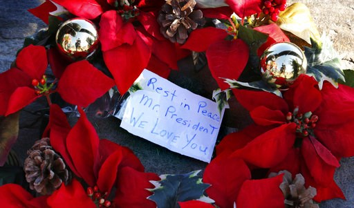 (AP Photo/Robert F. Bukaty). A wreath with a note to former President George H. W. Bush lay at a makeshift memorial across from Walker's Point, the Bush's summer home, Saturday, Dec. 1, 2018, in Kennebunkport, Maine. Bush died at the age of 94 on Frida...