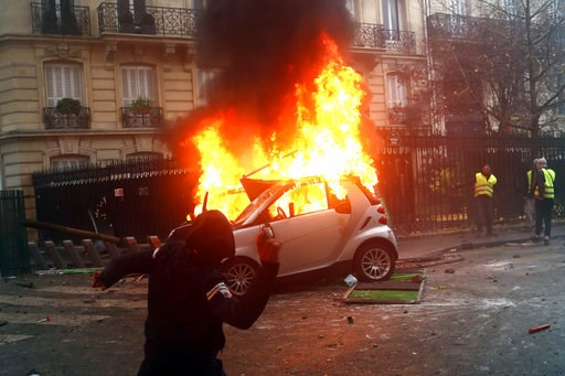 (AP Photo/Thibault Camus). A hooded demonstrator throws an item as a car buns during a demonstration Saturday, Dec.1, 2018 in Paris. Protesters angry about rising taxes clashed with French police for a third straight weekend and over 100 were arrested ...