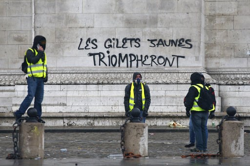 "(AP Photo/Thibault Camus). Demonstrators stand by the words ""yellow jackets will triumph"" written in black letters at the base of the Arc de Triomphe during a demonstration Saturday, Dec.1, 2018 in Paris. Paris police say at least 63 people have been a..."