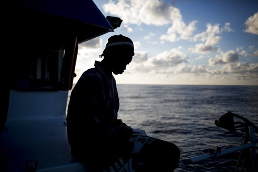 (AP Photo/Javier Fergo). In this Friday, Nov. 30, 2018, photo, a migrant from Senegal sits on the deck of a the Nuestra Madre de Loreto Spanish fishing vessel carrying 12 migrants rescued off the coast of Lybia. One of the migrants was evacuated by hel...