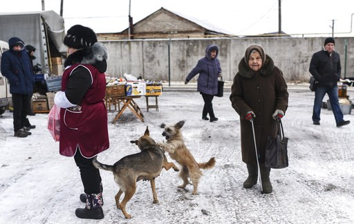 (AP Photo/Evgeniy Maloletka). Local people walk through at Saturday's market in Milove, a small town at the border between Ukraine and Russia, in Luhansk region, eastern Ukraine, Saturday, Dec. 1, 2018.