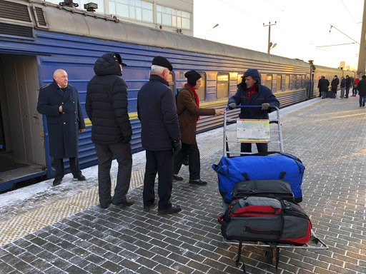 (AP Photo/Alexander Zemlianichenko). A porter helps passengers with their luggage as they arrive by a train from Odessa, Ukraine at Kievsky (Kiev) railway station in Moscow, Russia, Friday, Nov. 30, 2018. Ukrainian officials announced earlier on Friday...