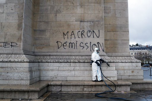 "(AP Photo/Thibault Camus). A worker is about to clean a graffiti reading "" Macron resignation"" on the Arc de Triomphe the day after a demonstration, in Paris, Sunday, Dec. 2, 2018. A protest against rising taxes and the high cost of living turned into ..."
