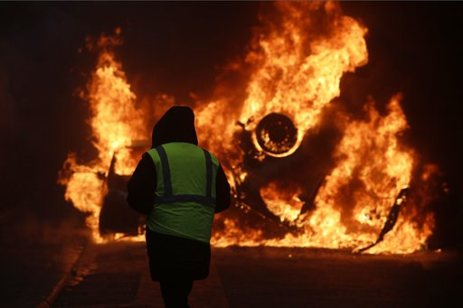 (AP Photo/Kamil Zihnioglu). A demonstrator watches a burning car near the Champs-Elysees avenue during a demonstration Saturday, Dec.1, 2018 in Paris. French authorities have deployed thousands of police on Paris' Champs-Elysees avenue to try to contai...