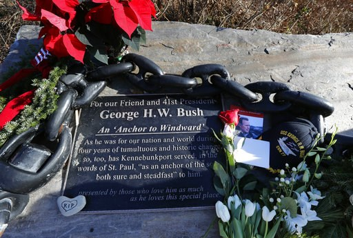 (AP Photo/Robert F. Bukaty). Flowers and mementoes lay near a plaque honoring former President George H. W. Bush at a makeshift memorial across from Walker's Point, the Bush's summer home, Saturday, Dec. 1, 2018, in Kennebunkport, Maine. Bush died at t...