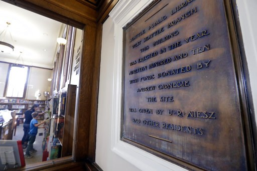 (AP Photo/Elaine Thompson). In this photo taken Wednesday, Oct. 10, 2018, library patrons look over books in view of a plaque honoring the Andrew Carnegie-built Seattle Public Library, one of six in the city still in use that were built with funds from...