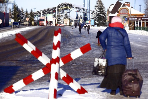 (AP Photo/Pavlo Pakhomenko). A woman walks to cross the checkpoint at the border with Russia in Hoptivka, Ukraine, Friday, Nov. 30, 2018. Ukrainian officials announced earlier on Friday that all Russian men aged between 16 and 60 will be barred from en...