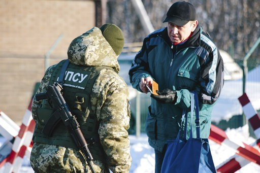 (AP Photo/Pavlo Pakhomenko). A Ukrainian border guard checks documents of a man who is going to cross the border to Russia at the checkpoint at the border with Russia in Hoptivka, Ukraine, Friday, Nov. 30, 2018. Ukrainian officials announced earlier on...