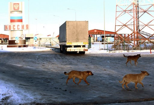 (AP Photo/Pavlo Pakhomenko). Stray dogs run past the checkpoint at the border with Russia in Hoptivka, Ukraine, Friday, Nov. 30, 2018. Ukrainian officials announced earlier on Friday that all Russian men aged between 16 and 60 will be barred from enter...