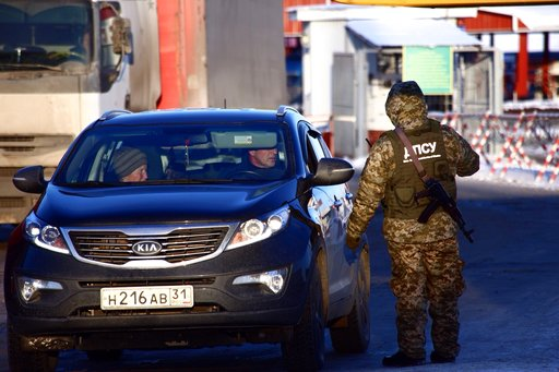 (AP Photo/Pavlo Pakhomenko). A Ukrainian border guard speaks to a driver of a car from Russia at the checkpoint at the border with Russia in Hoptivka, Ukraine, Friday, Nov. 30, 2018. Ukrainian officials announced earlier on Friday that all Russian men ...