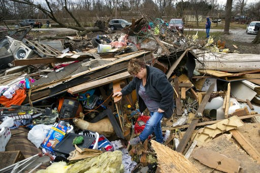 (Ted Schurter/The State Journal-Register via AP). Joyce Morrissey sorts through the debris of her nephew Stephen Tirpak's house in Taylorville, Ill., Sunday, Dec. 2, 2018. The National Weather Service says multiple tornadoes touched down in central Ill...