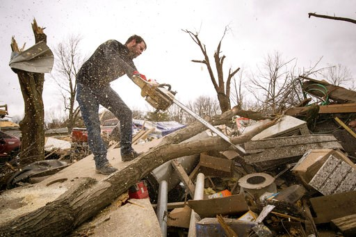 (Ted Schurter/The State Journal-Register via AP). Steven Tirpak uses a chainsaw to remove tree branches that fell onto his two-story home in Taylorville, Ill., Sunday, Dec. 2, 2018. The National Weather Service says multiple tornadoes touched down in c...